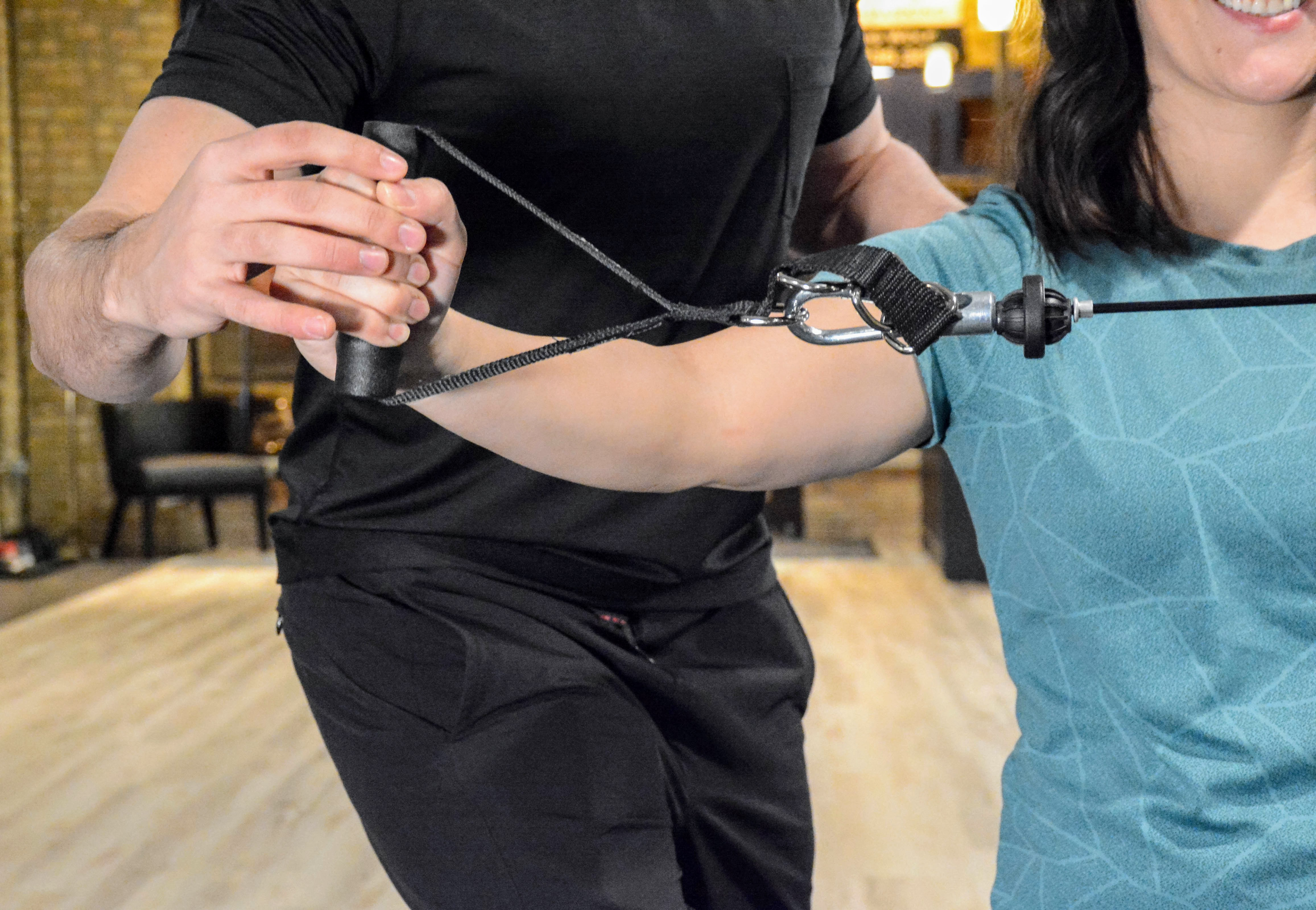 Woman doing an arm extension with cable during a personal training session