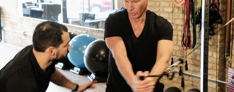 John works with a personal training client on arm and core exercises.