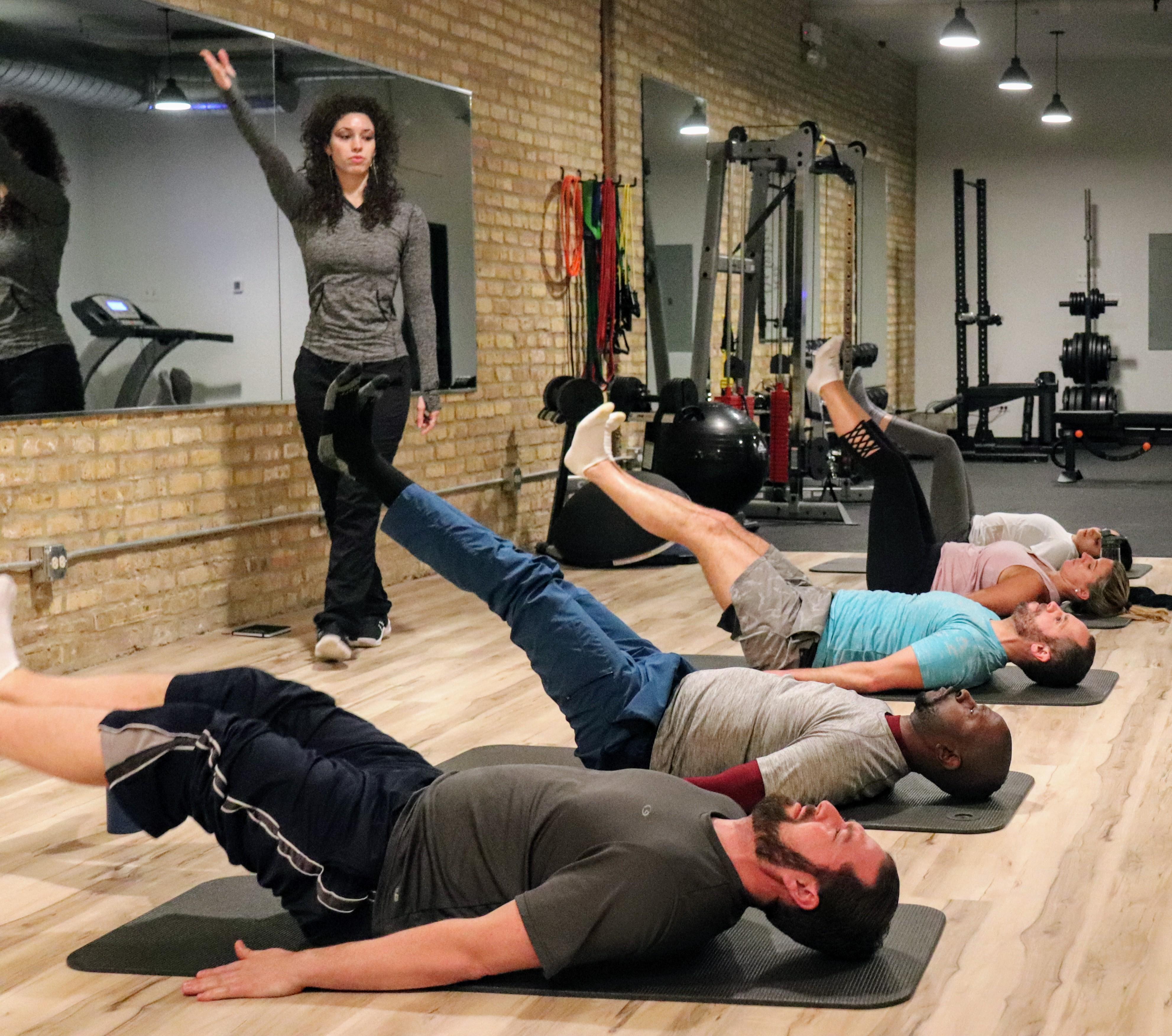 Mat Pilates class going through leg exercises