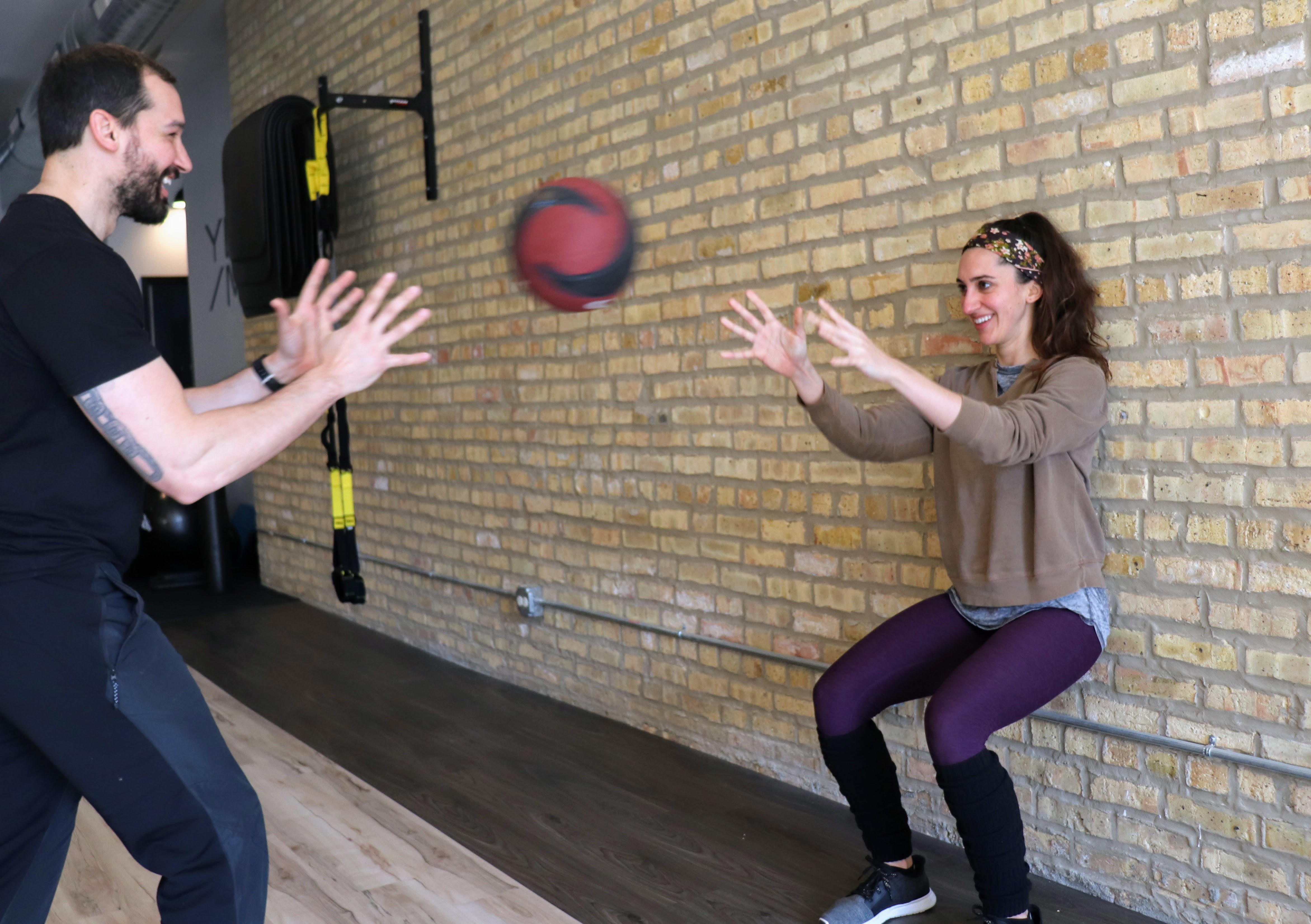 trainer and client pass ball back and forth while holding wall squat